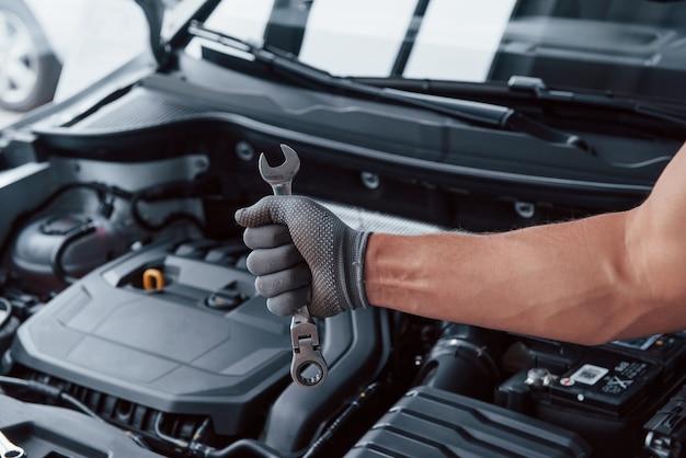 La mano dell'uomo in guanto tiene la chiave davanti all'automobile rotta Foto Gratuite