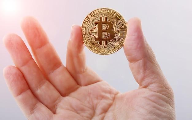 黄金のビットコインを持っている男の手 Premium写真