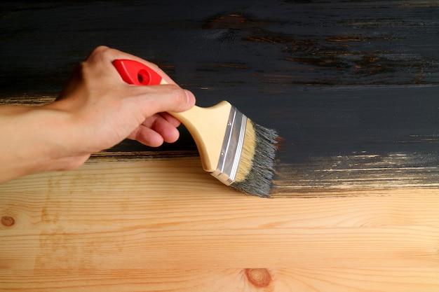 Man's hand holding brush painting wood plank with dark grey paint Premium Photo