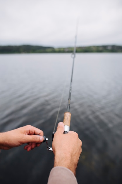 Man's hand holding fishing rod in front of lake Free Photo