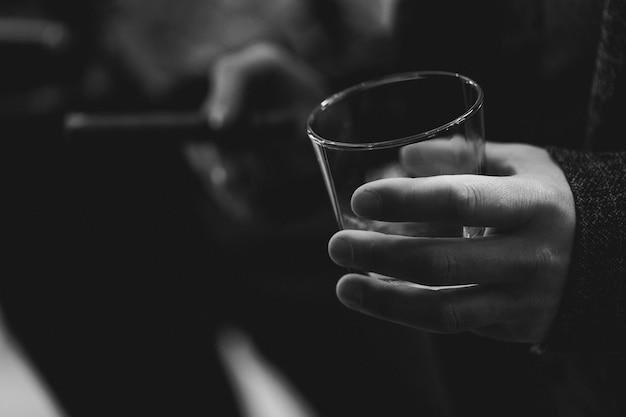 Man's hand holding glass of whiskey. black and white Premium Photo