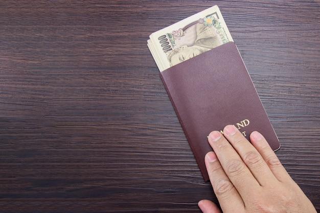 茶色の暗い木製のテーブルに国際パスポートと日本のお金を持っている男の手。 Premium写真