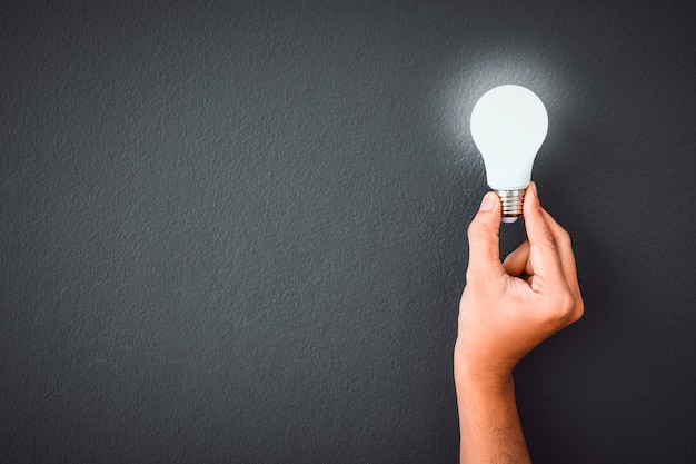 Man's hand holding led light bulb over black color wall background Premium Photo
