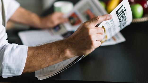 Man's hand holding newspaper Free Photo
