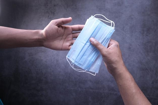 Мужская рука держит защитную маску сверху вниз Premium Фотографии