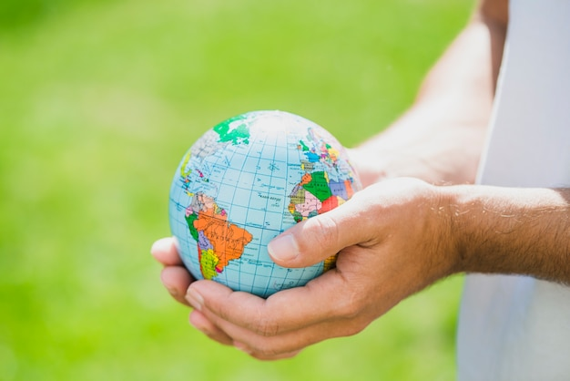 Man's hand holding small globe Free Photo