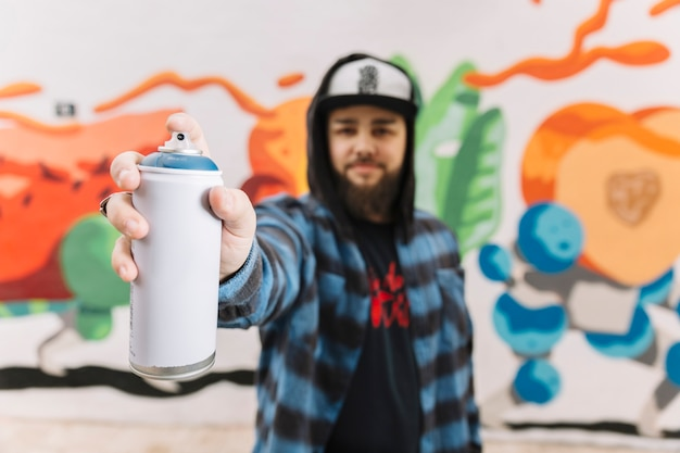 Man's hand holding white aerosol can Free Photo