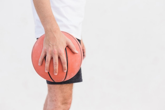 Man's hand holdng basketball Free Photo