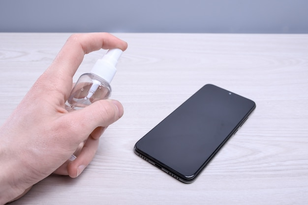 A man's hand holds and snaps a disinfectant spray and disinfect the phone to disinfect various surfaces that people touch.antibacterial antiseptic gel for hands Premium Photo