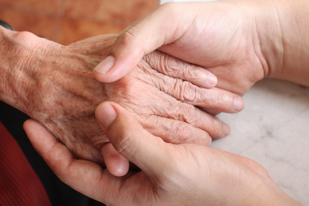 The man's hand is holding the old woman hand. Premium Photo