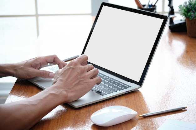 Man's hand is typing a keyboard on the laptop. Premium Photo