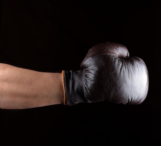Man's hand is wearing a brown leather boxing glove Premium Photo