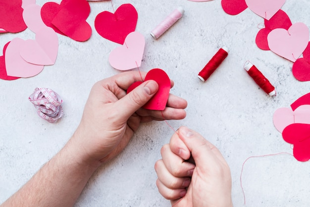 Man's hand making the red and pink paper heart shape garland with thread on white background Free Photo