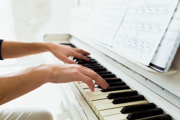 Man's hand playing piano with musical notes Free Photo
