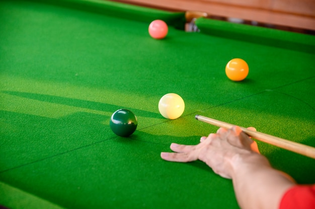 Man's hand playing snooker in bar with snooker ball Premium Photo