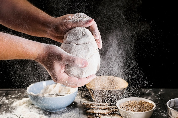 Man's hand preparing dough with ingredients on the table Free Photo