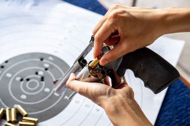 Man's hand reloading pistol revolver with bullets and target Premium Photo