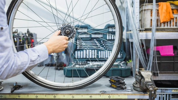 Man's hand repairing wheel of bicycle Free Photo