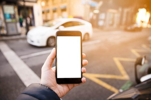 Man's hand showing the mobile phone with white screen display on road Free Photo
