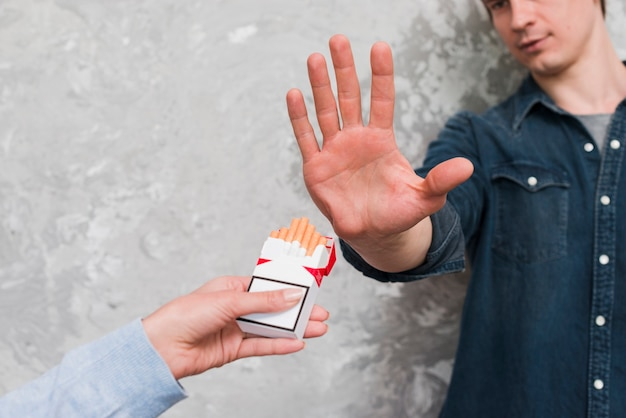 Man's hand showing stop gesturing to woman offering packet of cigarette Free Photo