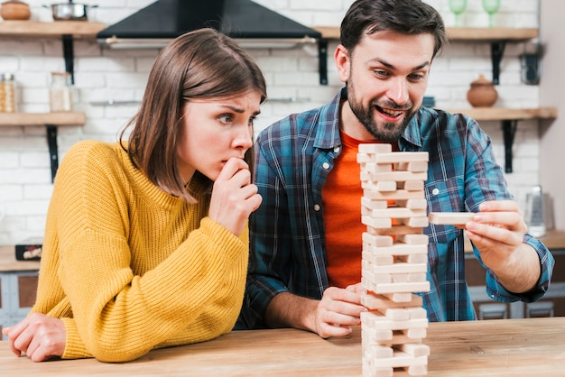 Man's hand taking or putting a block to an unstable and incomplete tower of wooden blocks Free Photo