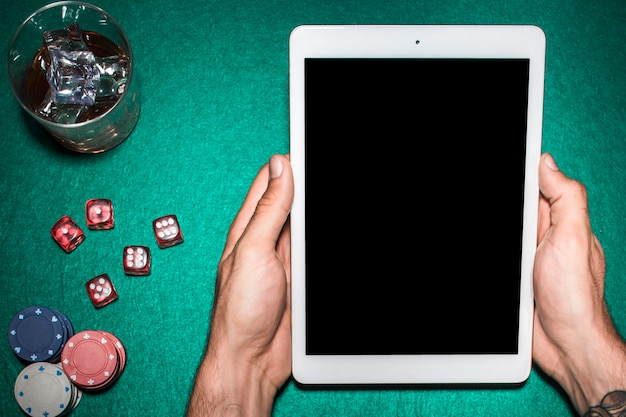 Man's hand using digital tablet over the poker table with whiskey glass Free Photo