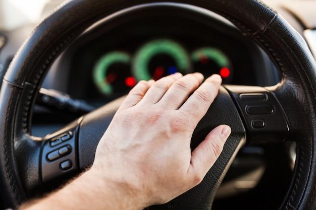 Man's hand on the wheel of the car Premium Photo