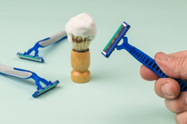 A man's hand with a disposable razor on the background of shaving accessories Premium Photo