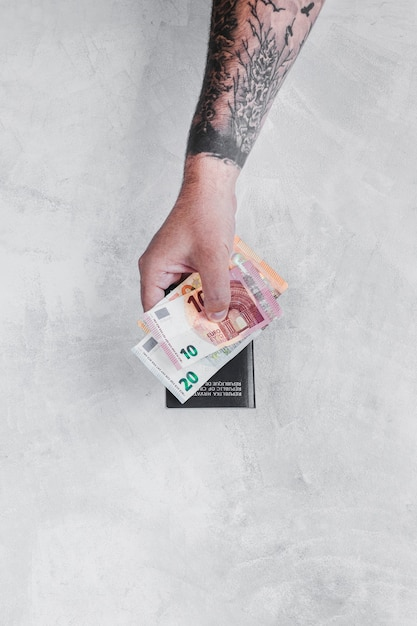 Man's Hand With Tattoo Holding Euro Notes And Passport