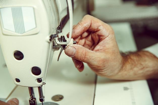 Мужские руки и швейная машина. кожаная мастерская. текстиль винтажный индустриальный. мужчина в женской профессии. концепция гендерного равенства Бесплатные Фотографии