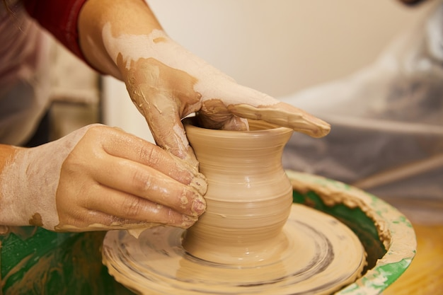 Man's hands are moulding a vase in a pottery workplace Free Photo