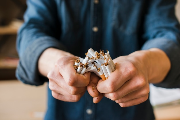 Man's hands breaking bunch of cigarettes Free Photo