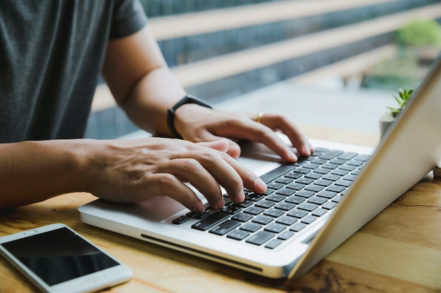 Man's hands busy working on his laptop sitting at wooden table Premium Photo