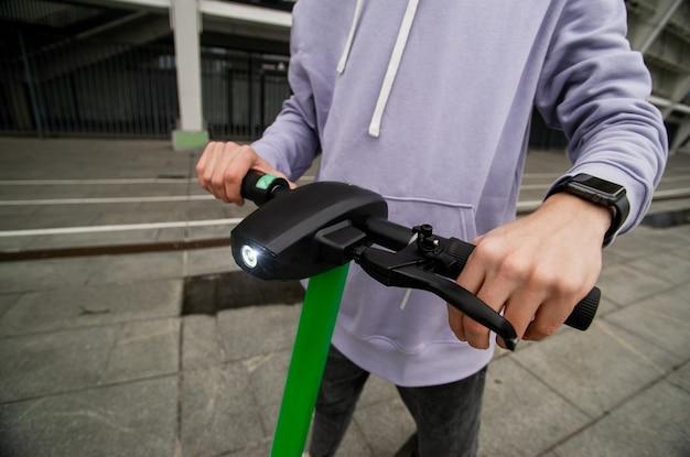 男の手は電動スクーターのハンドルを握っています。簡単運転コンセプト。カジュアルな灰色のフーディの男は、街を旅するために電気自動車を借りました。環境にやさしい輸送コンセプト。 Premium写真