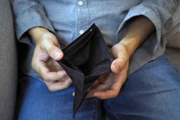 Man's hands open empty purse, poverty, debt and bankruptcy in the payment of bills and credit cards Premium Photo