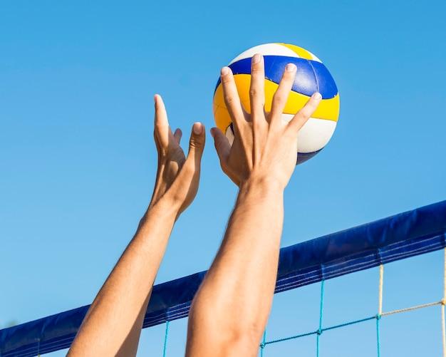 Le mani dell'uomo si preparano a colpire la pallavolo in arrivo sulla rete Foto Gratuite