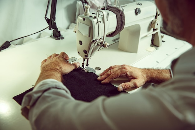 Man's hands behind sewing. leather workshop. textile vintage industrial. the man in female profession. gender equality concept Free Photo