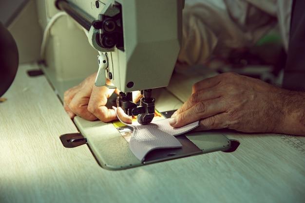 Mani dell'uomo dietro la cucitura. laboratorio di pelletteria. tessile industriale vintage. l'uomo nella professione femminile. concetto di uguaglianza di genere Foto Gratuite