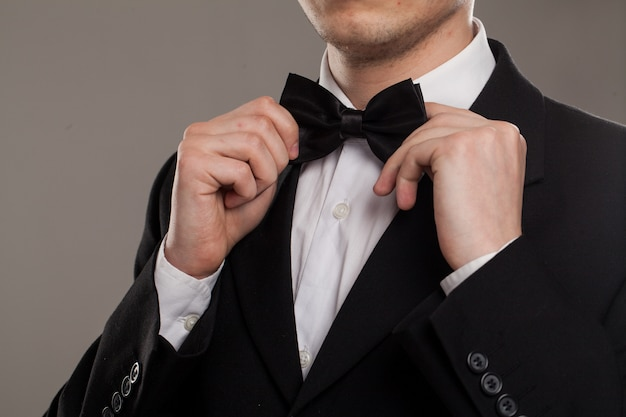 Man's hands touches bow-tie Free Photo