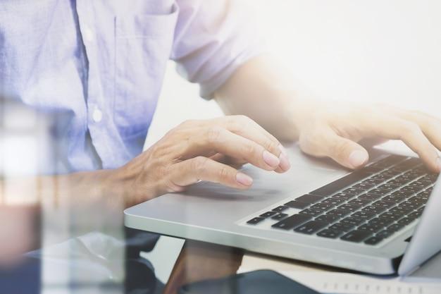 Man's hands typing on laptop keyboard. Free Photo