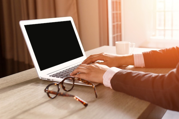 Man's hands using laptop with blank screen on desk in home interior. Premium Photo