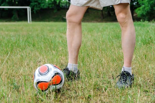 Ноги человека на траве рядом с футбольным мячом Premium Фотографии