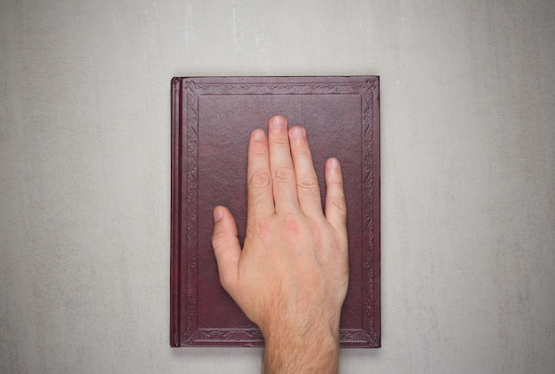 A man's palm on a book, an oath on the bible. Premium Photo