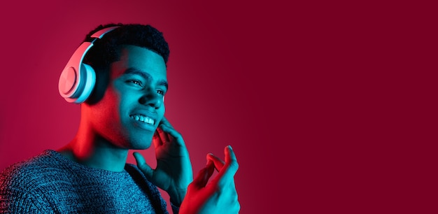 Man's portrait on red studio wall in multicolored neon light Free Photo