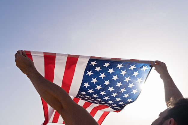 Man's raised hands with waving american flag against clear blue sky Premium Photo