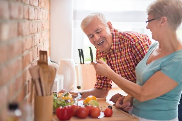 彼の妻によって調理された夕食をサンプリングする男 無料写真