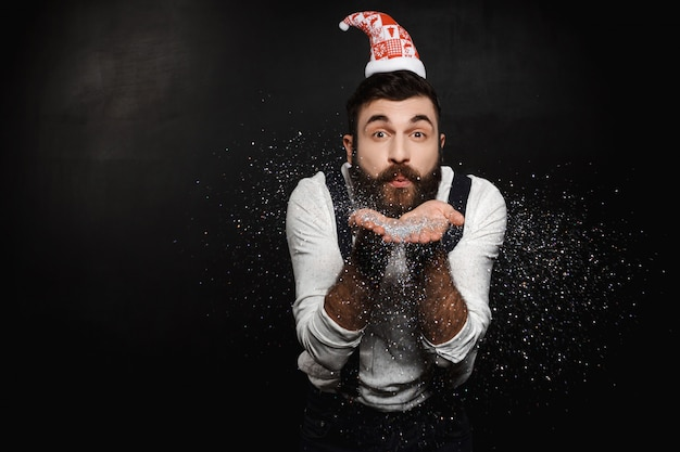 Man in santa claus hat blowing silver glitter over black. Free Photo
