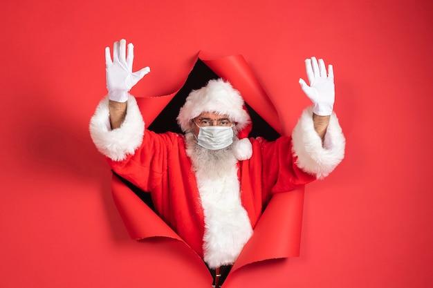 Uomo in costume da babbo natale con mascherina medica che esce di carta Foto Gratuite