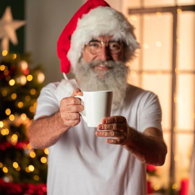 Uomo in tazza della holding del cappello della santa Foto Gratuite