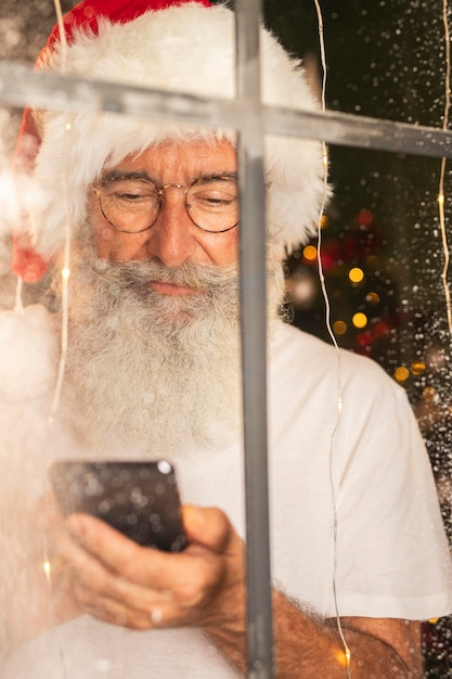 Uomo in santa hat utilizza lo smartphone attraverso la finestra Foto Gratuite